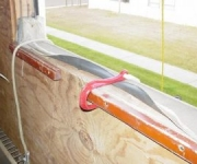 Survival hook at window sill, which is securing a firefighter as he slides to safety below.