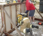 "Firefighter practicing the ""Wall Breach"" under the watchful eye of a Fire Command instructor."