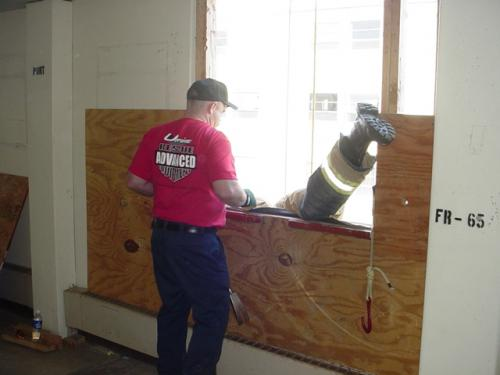"Firefighter exiting the window using the ""Emergency Rope Slide"" with a Fire Command instructor looking on."