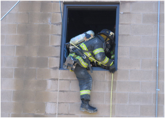 A firefighter preparing to descend using a firefighter escape system.