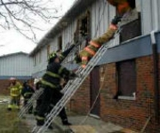 """Fire Command instructors guiding student firefighter through the """"Ladder Bail"""" evolution."""